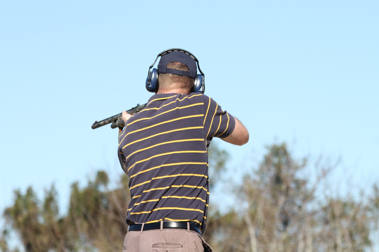 man in a striped shirt and ear protection skeet shooting with a shotgun