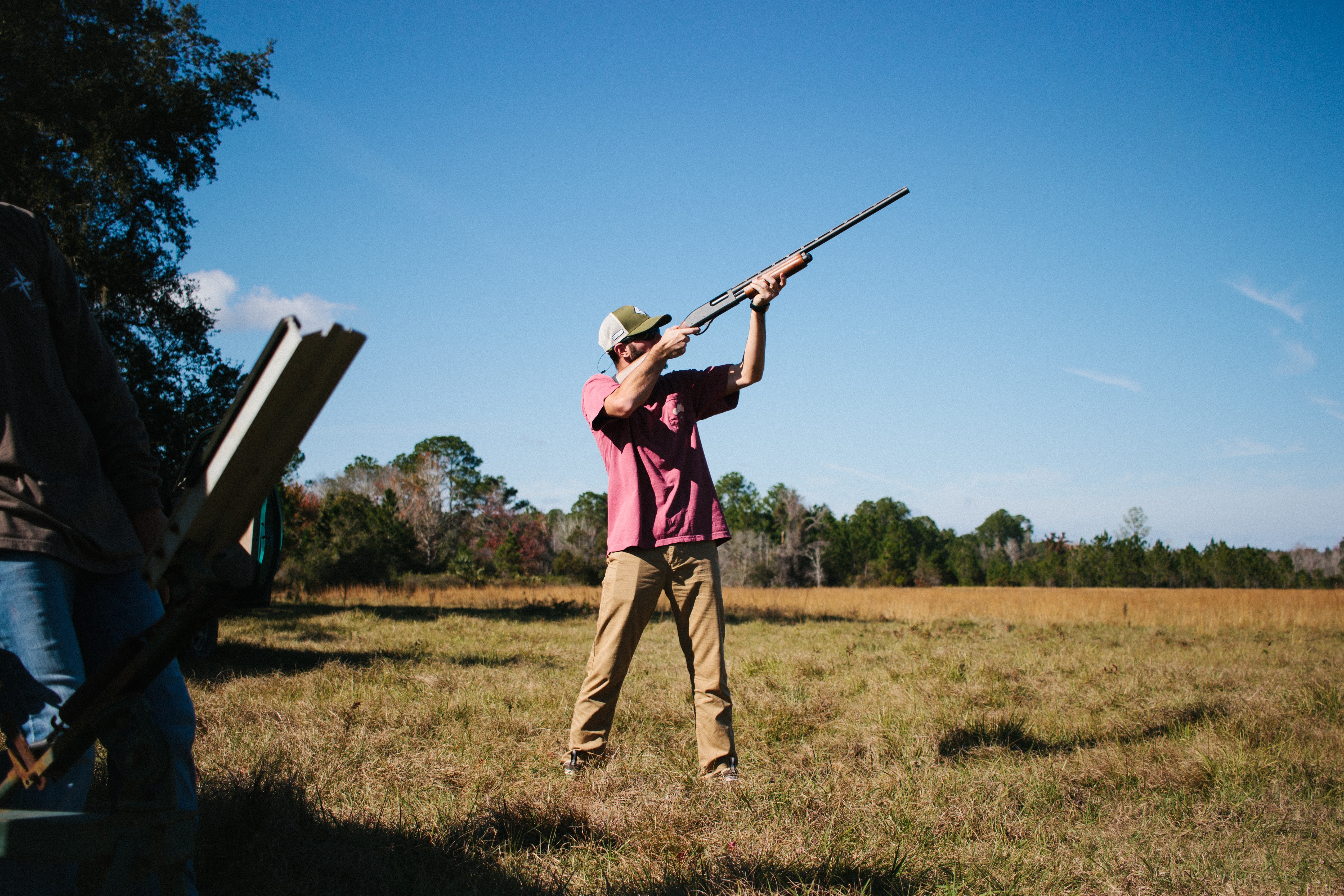 man shooting on clay pigeons